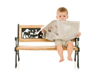 little boy reading a newspaper